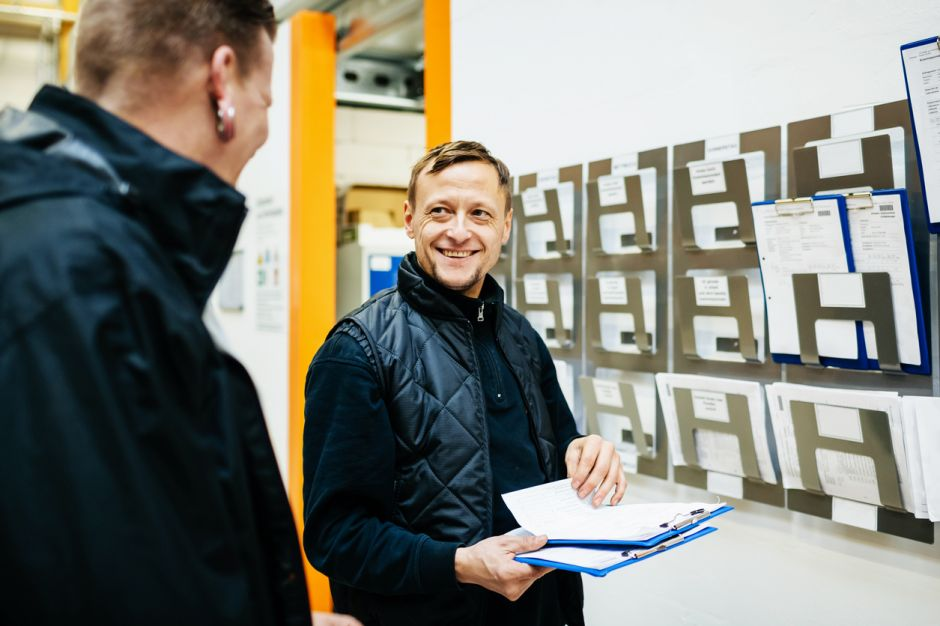 A warehouse manager smiling as he chats to his colleague while organising their workload and schedule for the week.
